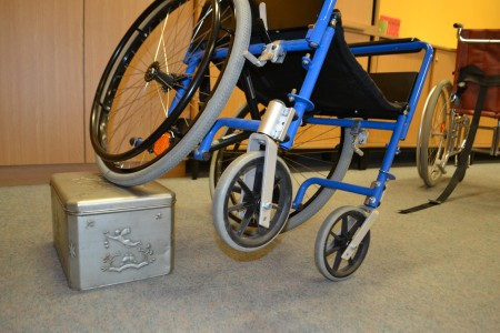 Ein Rollstuhl kippelt auf einer Kiste.