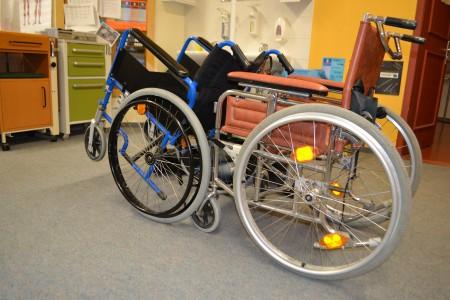Ein Rollstuhl steht nach hinten gekippt an einem zweiten Rollstuhl, der ihn vorm Umkippen hält.