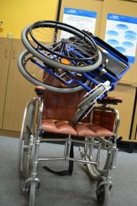 Ein Rollstuhl steht ausgeklappt und der andere zusammengeklappt auf ihm.