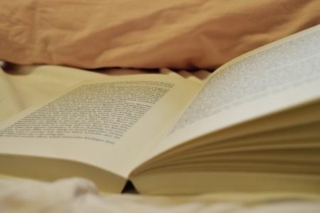 aufgeschlagenes Buch liegt auf einem Bett
