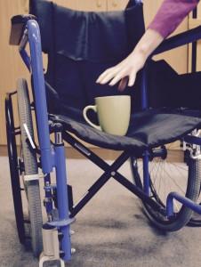Eine Kaffeetasse steht auf einem Rollstuhl. Eine Hand greift nach der Tasse.