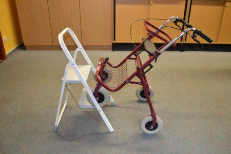 Rollator steht mit den vorderen Rädern auf einet Leiter