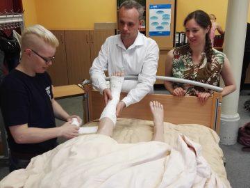 Drei Schüler in der Schule lernen einen verbandswechsel an einer plegepuppe