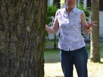 eine ältere Dame steht an einem Baum in der Sonne