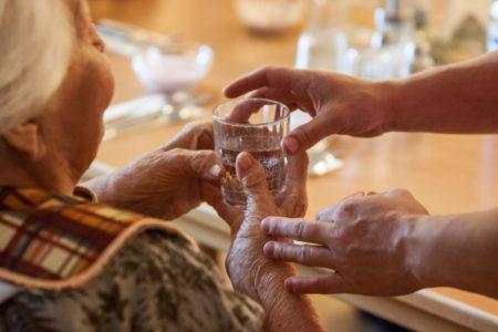 Pflegefachkraft reicht Seniorin ein Glas Wasser und Medikamente